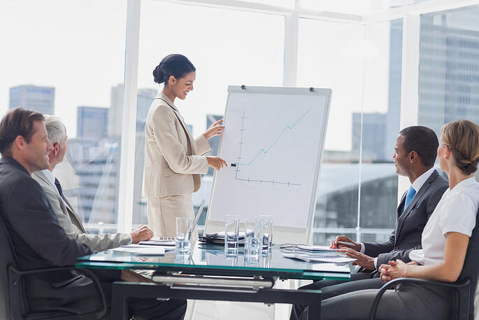 Businesswoman pointing at a growing chart during a meeting in the meeting room